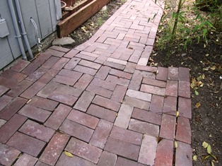 The brick walkway runs past the construction of the new front porch (still in progress)