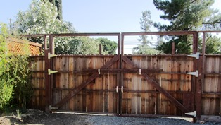 The wooden gate swings open so that a truck or bobcat can get through
