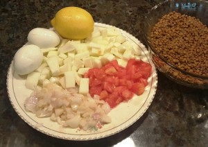 Ingredients for lentil salad include sauteed onions, heirloom tomato, zucchini, hard-boiled eggs, and fresh lemon juice