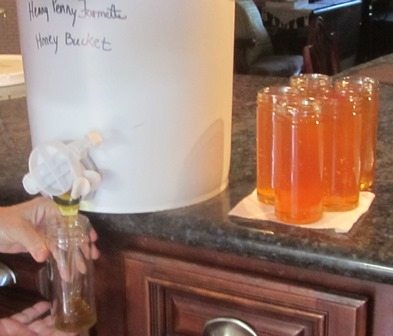 Honey from a bottling bucket is drained into sterile jars